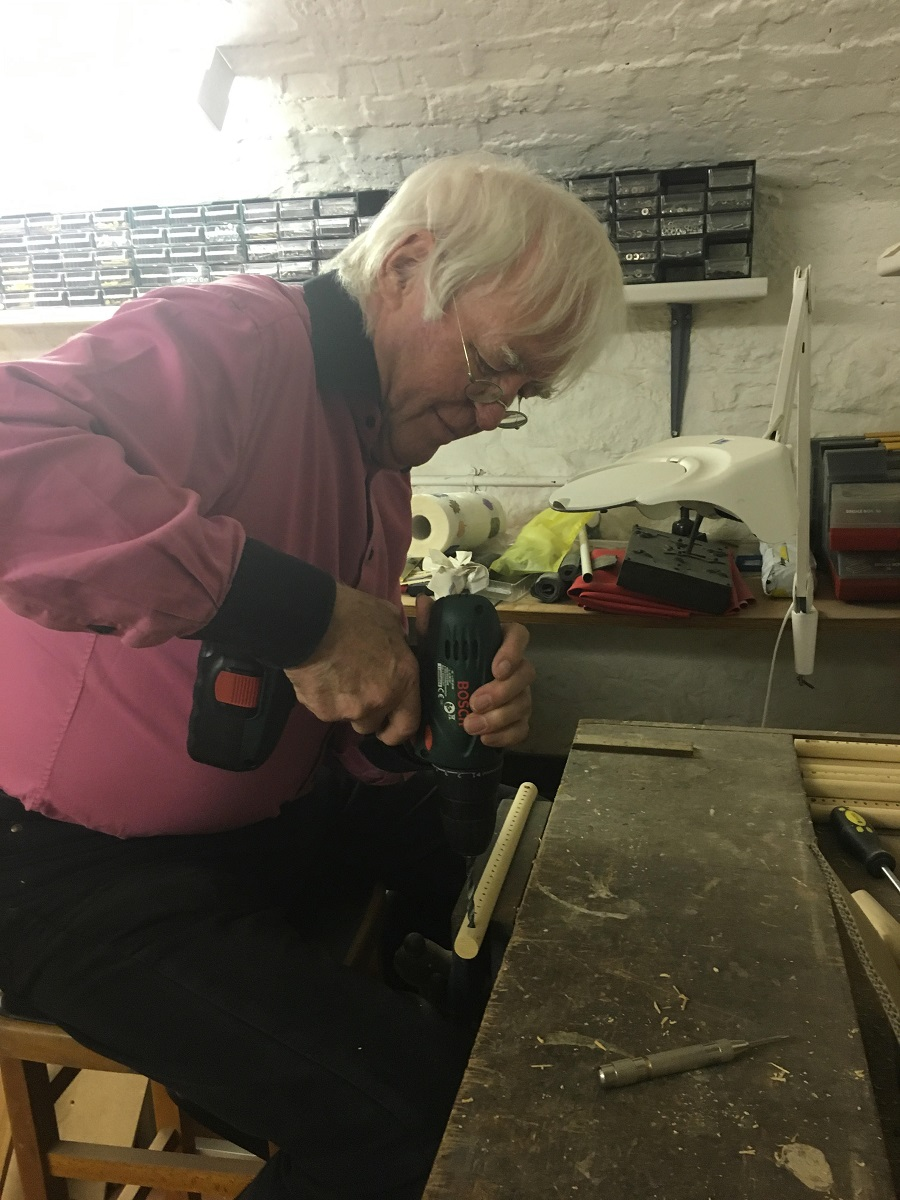 Photo of my father, Professor Iann Barron CBE, drilling holes into the dowels in his workshop.